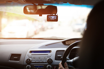 Front camera car recorder, woman driving a car  with video recorder next to a rear view mirror