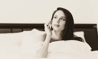 photo of the beautiful young woman lying on the bed and talking on the mobile phone