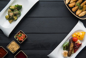 salads, vegetable food and gravy in plates on a black wooden background
