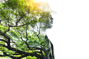 double exposure image of the engineer thinking during sunrise overlay with forest image and white copy space. the concept of clean energy, futuristic, industrial4.0 and hydroelectric.