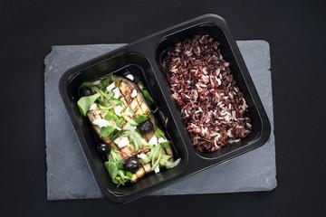 Jedzenie na wynos. Grillowany bakłażan z czarnymi oliwkami, serem feta i zielonymi warzywami podany z dzikim ryżem