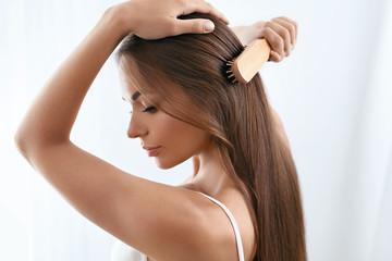 Beauty Hair Care. Beautiful Woman Brushing Long Healthy Hair
