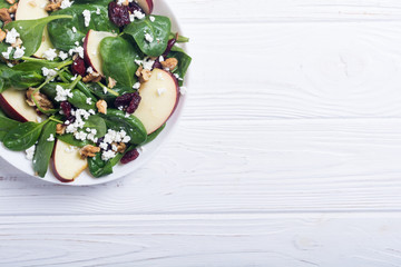 Autumn spinach salad with apple , cheese , walnut and dried cranberry