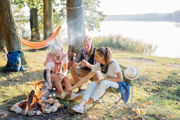 Best friends enjoying bonfire on hike near the lake on summer holidays. Camping on the background