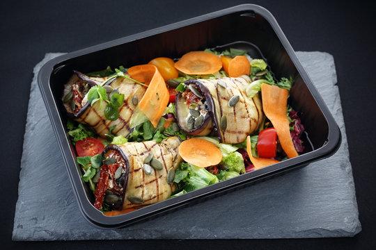 Dieta pudełkowa. Roladki z grillowanego bakłażana z suszonymi pomidorami i serem podane na sałacie i marchewce zapakowane w pojemnik na żywność.