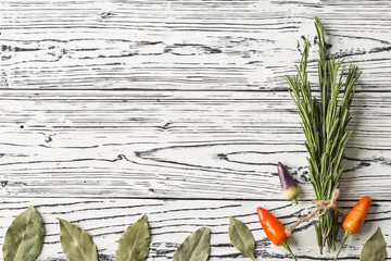 chili pepper and rosemary sprigs with laurel leaves on wooden b
