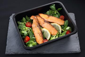 Grillowany łosoś na sałacie. Gotowe danie na wynos zapakowane w lunch box.