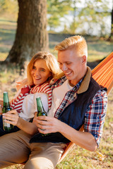 Young couple having fun outdoors with bottles of beer in their hands