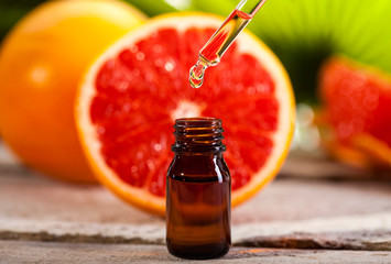Grapefruit Essential Oil on green leaves background