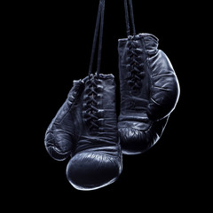 Wall Mural - Old boxing gloves on an isolated black background