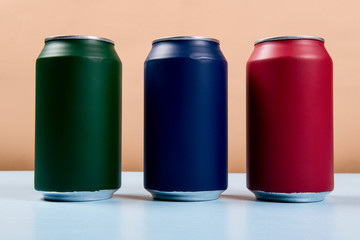 three colored cans of soft drinks closed on a light blue background