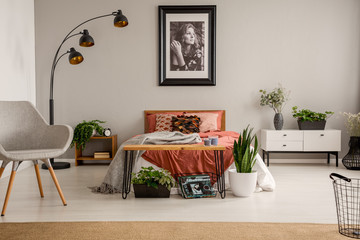Stylish grey chair, black lamp, poster on the wall and king size bed with rust color bedding in bright bedroom of stylish flat, real photo with copy space on the grey wall