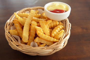 French fries in a basket are placed on the table.
