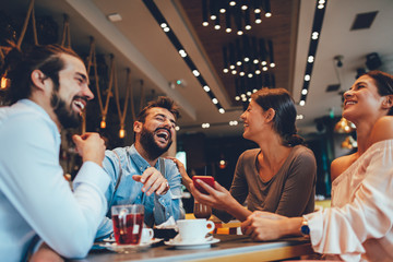 Group of Happy friends having with smartphone in cafe