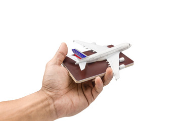 Hand holding a model plane and passport