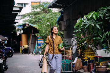 Beautiful smiling Thai woman walking on the street and carrying watermelon and a bouquet.