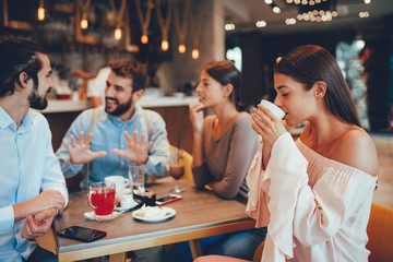 Young woman enjoys coffee with friends in a cafe