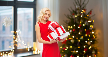 people and holidays concept - happy young woman in red dress holding gift boxes over home room with christmas tree background