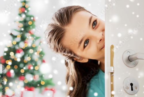 christmas and people concept - happy smiling beautiful girl looking out open door at home