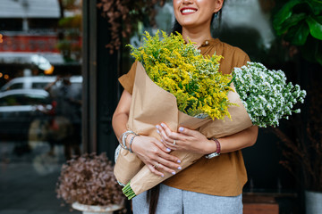 Hands of unrecognisable woman standing outdoors and holding fresh flowers.