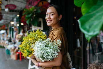 Smiling young woman holding flower bouquet outdoors