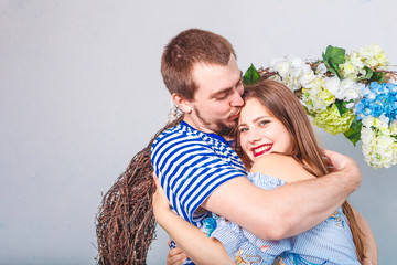 A young cheerful smiling couple hugging in light blue room studio. Love and happy family