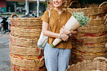 Cropped smiling Asian woman holding a bouquet and standing outdoors by the woven baskets.