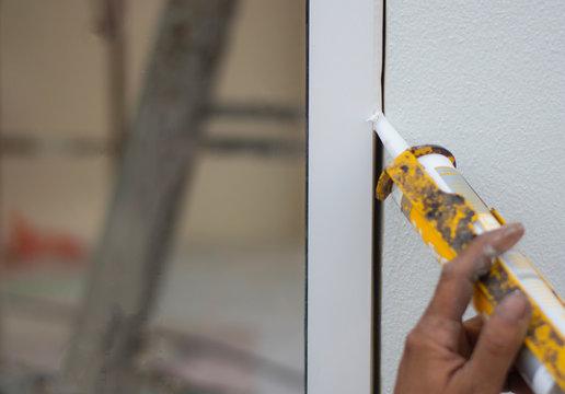Repairman's hand installing the windows with gun silicone. closeup