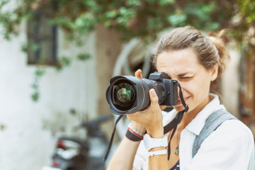 Beautiful young woman with a camera in her hands, professional at work