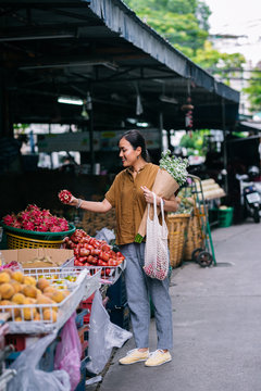 Pretty Asian woman shopping on fruit market and holding flowers.