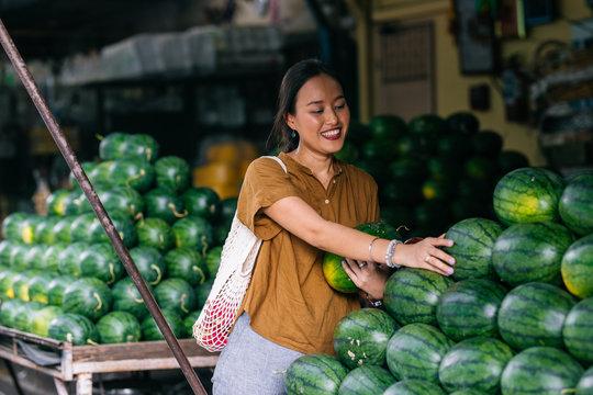Beautiful smiling Thai woman picking watermelon on food market.