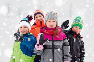 childhood, friendship and season concept - group of happy little kids in winter clothes outdoors