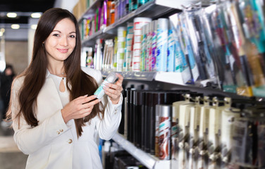 Smiling young female choosing haircare spray and other products at the shop
