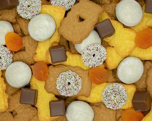 Weihnachtshintergrund aus verschiedenen Sorten von Weihnachtsplätzchen, Dominosteinen und getrockneten Aprikosen