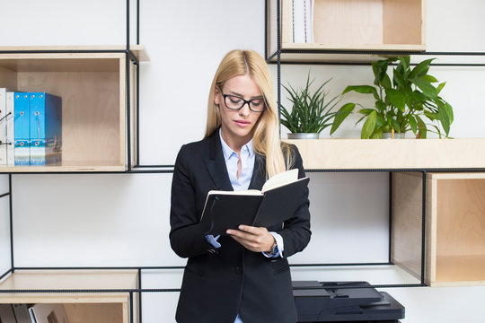 Young businesswoman with agenda standing in modern office