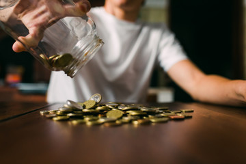 Crop guy spilling coins from jar