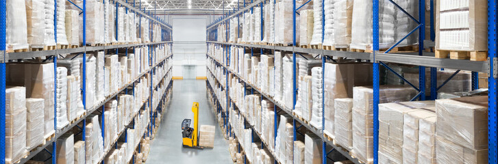 Large distribution warehouse passway with high shelves and forklift
