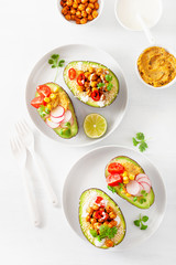 avocado boats stuffed with hummus, tomatoes, radish, roasted chickpea