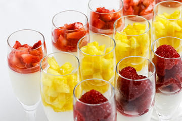 Rows of fruit and cream desserts in glass flutes on white.
