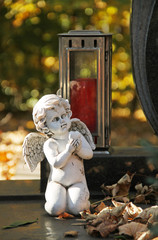 white angel and red lantern on the grave on the cemetery in autumn in Trinec, Czech Republic