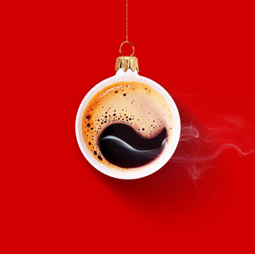 Christmas toy is made from a fragrant cup of coffee. Christmas toy. Holiday concept. Fragrant coffee on a red background for your advertising. Smoke from hot coffee.