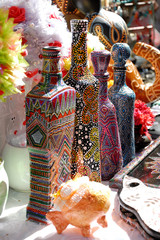 Many Different Glass Bottles Painted With Multicolor Dots