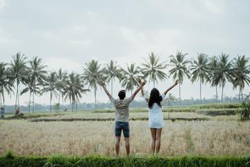 wo couple raising their arm while enjoy paddy rice field