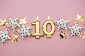 Number 10 gold candle and stars on a pastel pink background