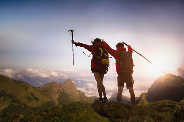 Two Hikers with backpacks standing to stay and relaxing on top of a mountain and enjoying the view of fog in the valley with a sunrise. Wall mural