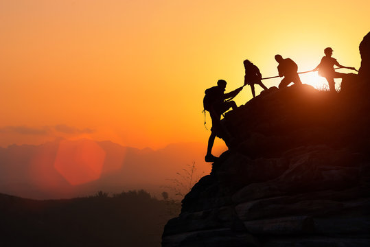Silhouette of the climbing team helping each other while climbing up in a sunset. The concept of aid.