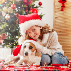 Child with dog near christmas tree