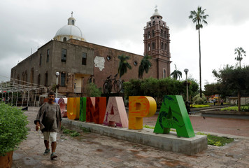 A man walks past a sign at the park in Escuinapa, near the southern tip of Sinaloa state after Hurricane Willa hit the area