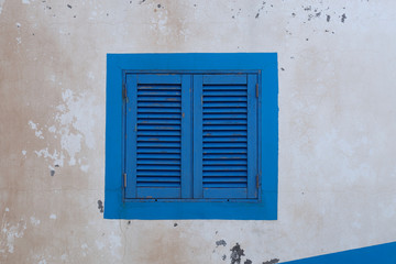 Blue wood window on an old white wall