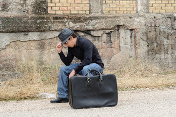 hombre sentado sobre maleta tocandose el sombrero